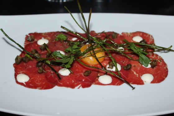beef carpaccio with fried chives and capers, with a 64 degree egg
